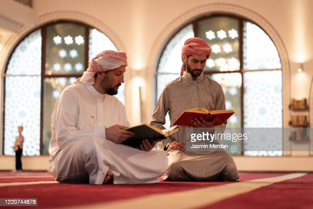 two arab adults reading koran in mosque - koran stock pictures, royalty-free photos & images
