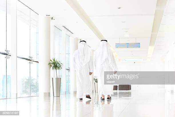 Two arab business men walking, talking, meeting
