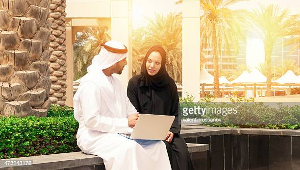 Two arab business people outside using laptop