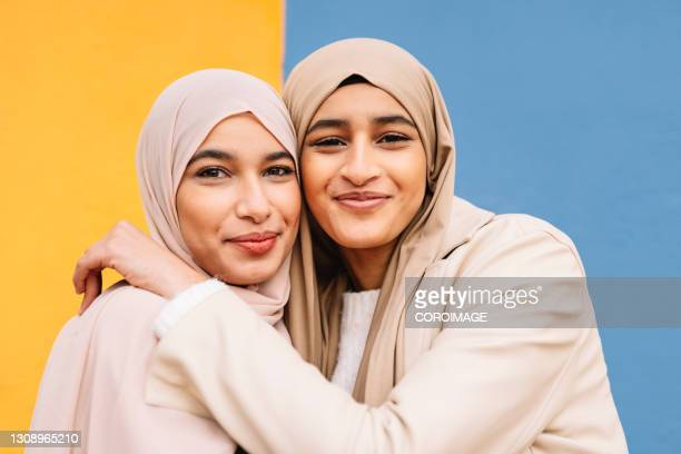 two arab female friends hugging each other outdoors. - united arab emirates stock pictures, royalty-free photos & images