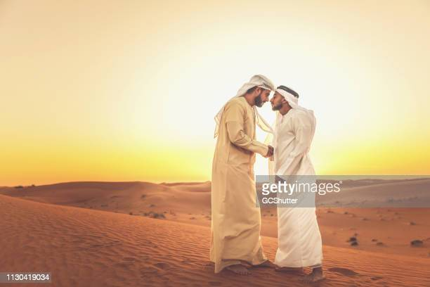 two arab men greeting each other on the sand dunes - tradition stock pictures, royalty-free photos & images
