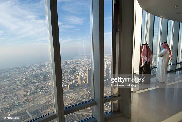 Two Arab men looking over Dubai from the Burj Khalifa