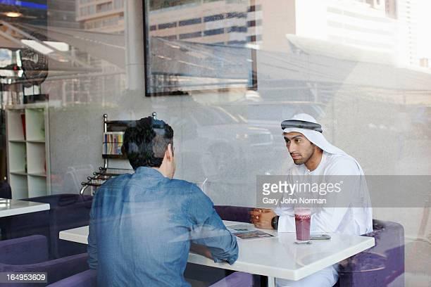 two arab men meeting in healthy food restaurant