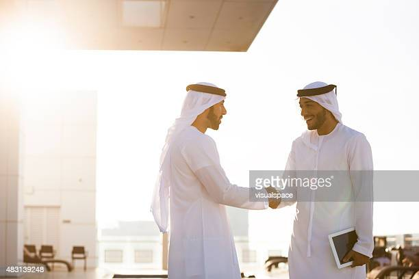 two arab men shaking hands - united arab emirates stock pictures, royalty-free photos & images