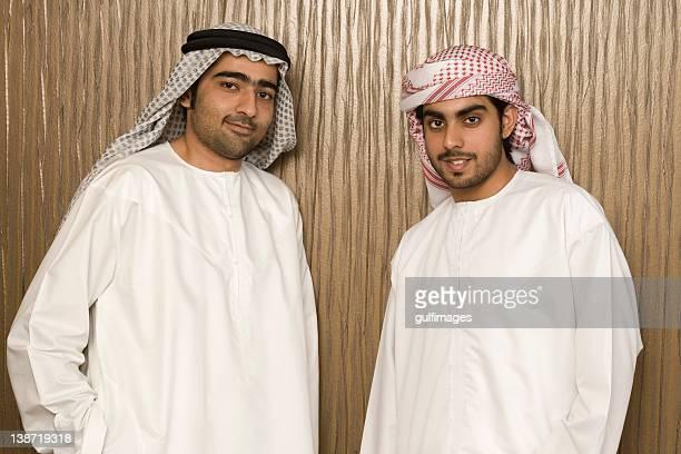 Two Arab men standing near the office wall,portrait