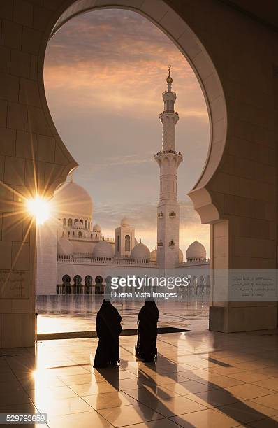 Two arab women entering a Mosque at sunset