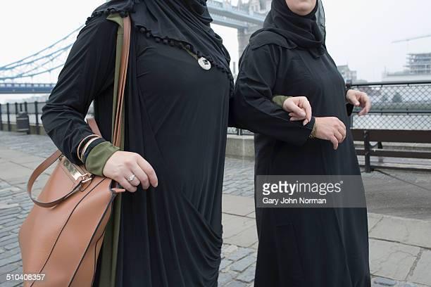 Two arab women walking past Tower Bridge in London