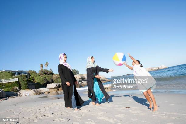 Two Arab women watching girl playing with ball on beach.