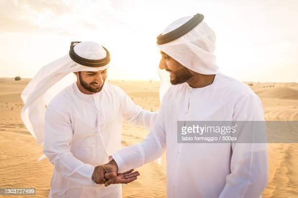 two arabic men together in desert,dubai,united arab emirates - gulf countries stock-fotos und bilder