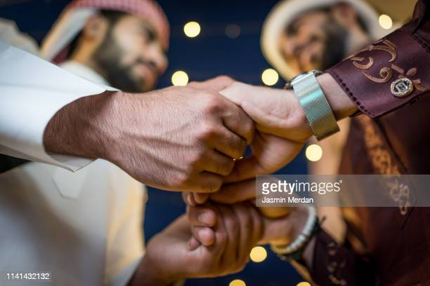 two arabs holding hands - ramadan stock pictures, royalty-free photos & images