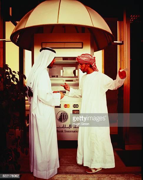 two arabs in conversation in front of a cash dispenser - hugh sitton fotografías e imágenes de stock