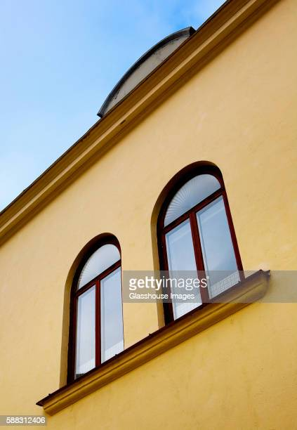 two arched windows on yellow facade, low angle view - wall building feature stock pictures, royalty-free photos & images