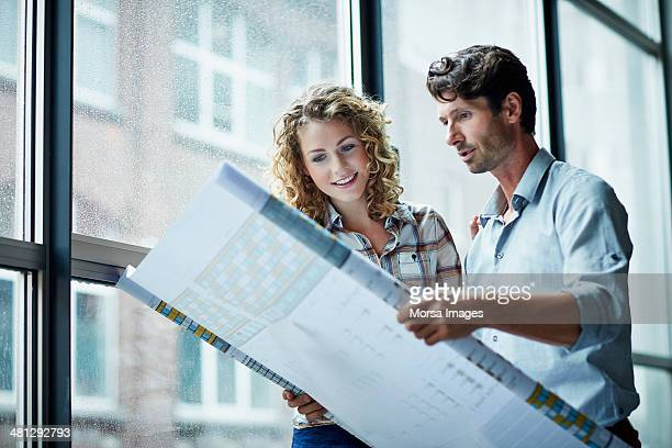 two architects checking blueprint - architect stockfoto's en -beelden