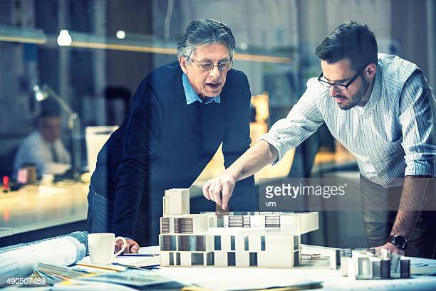 two architects discussing new project - architect stockfoto's en -beelden