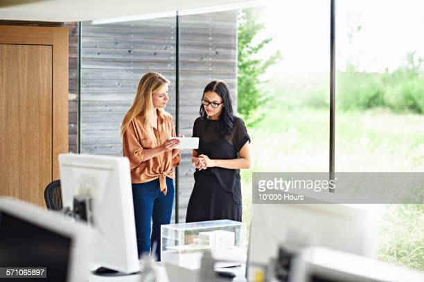 two architects discussing plans in a digital table - colleague photos et images de collection