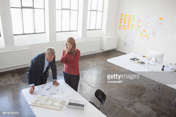 Two architects discussing project in office