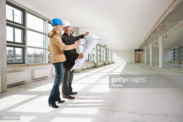 Two architects examining office building