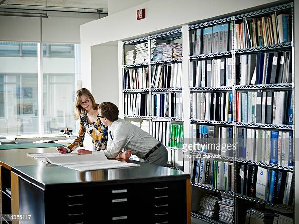 Two architects examining plans at desk in office