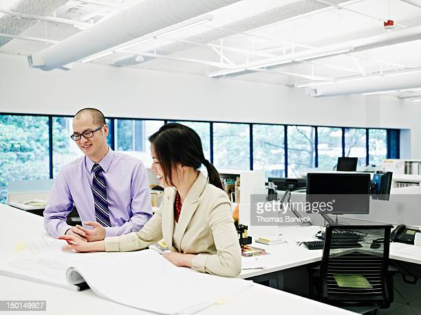 Two architects examining plans in office