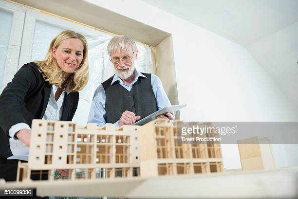 Two architects looking at architectural model