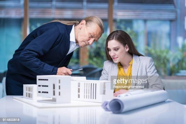 Zwei Architekten schauen sich ihre Modelle detalliert an