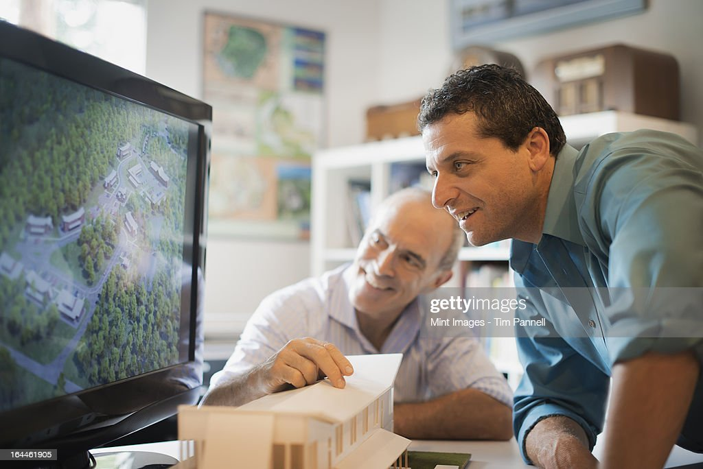 Two architects working on a green construction project, using computer technology. Scale model of a building. Computer design. : Stock Photo