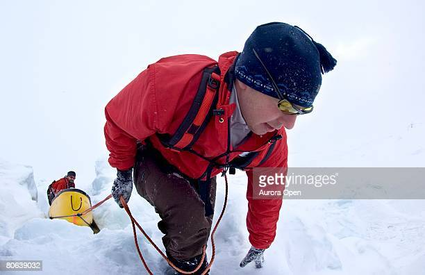 Two Arctic explores struggling to help each other over a pressure ridge in the middle of the Canadian barren landscape.