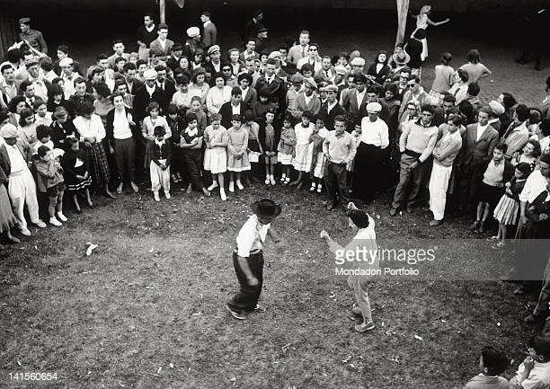 Two Argentine 'gato' dancers dancing surrounded by an attentive crowd Argentina November 1957
