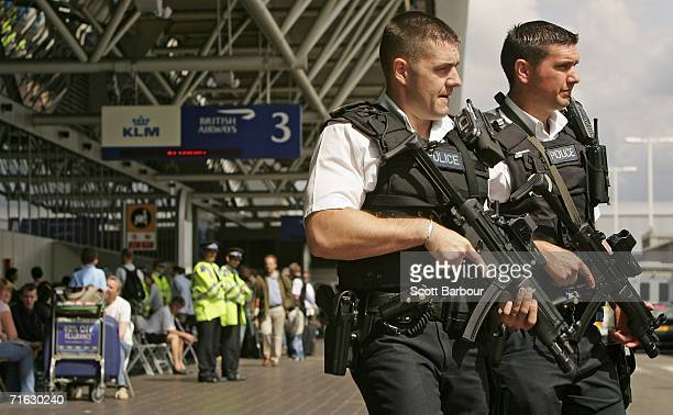 Two armed British police officers patrol outside of Heathrow Airport Terminal Four on August 11 2006 in London England The UK security threat level...