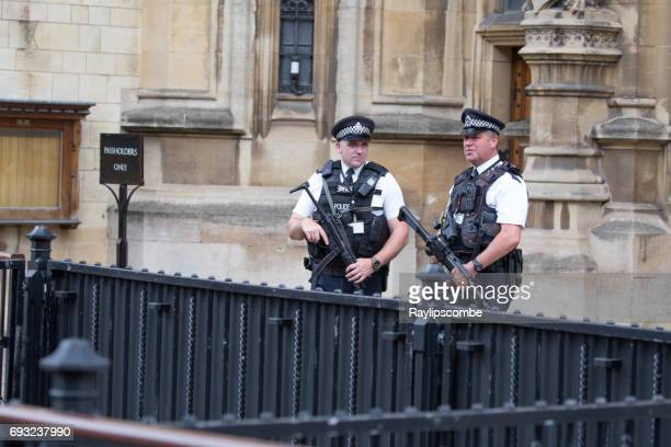 Two armed policemen standing guard outside the Houses of Parliament, Westminster, London England