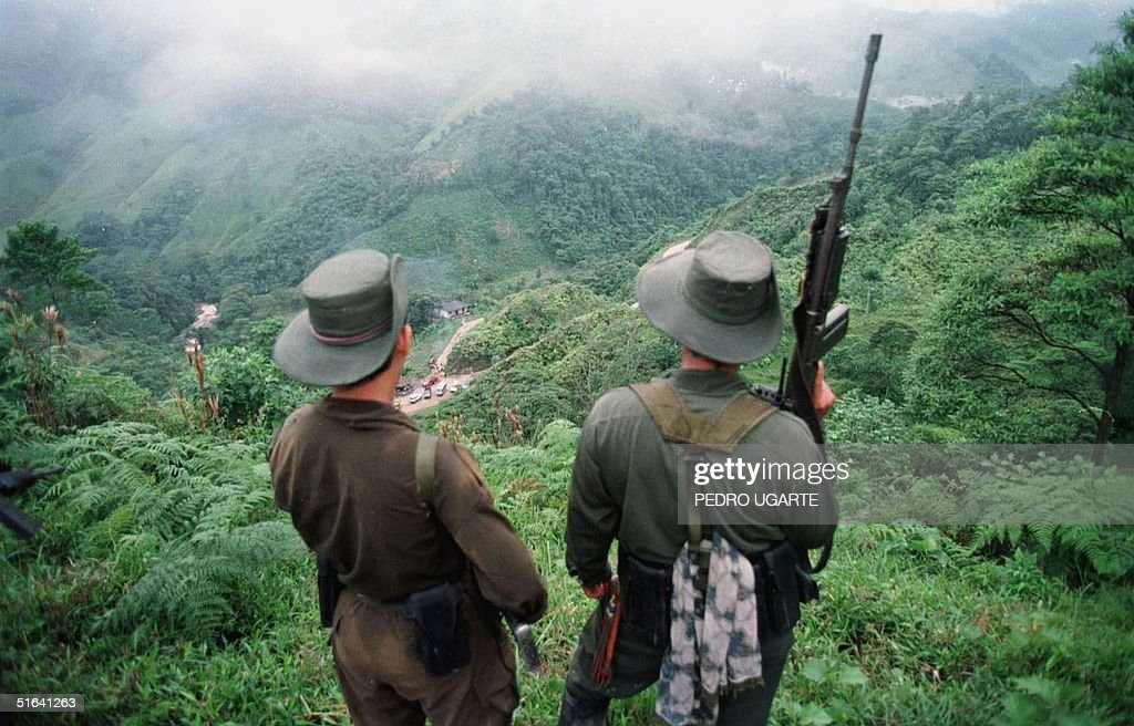 Two armed soldiers belonging to the Revolutionry Armed Forces of Colombia (FARC) monitor the Berlin pass, 07 March, near Florencia, in the southern Caqueta province of Colombia, where cars are prevented from going through after the rebels decreed 06 March a ban on 'travel on roads and waterways for six days'. The rebels try to dissuade voters from casting their ballots in the 08 March elections for congress. According to the rebels, the elections 08 March are illegitimate because the left has been forced out of national politics, following the murder over the past years of thousands of Colombia's left-wing politicians and supporters.