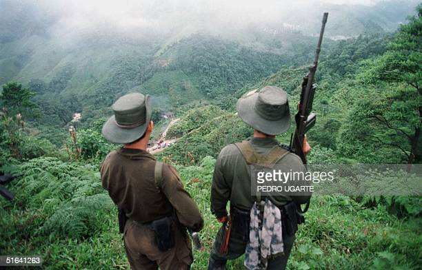 Two armed soldiers belonging to the Revolutionry Armed Forces of Colombia monitor the Berlin pass 07 March near Florencia in the southern Caqueta...