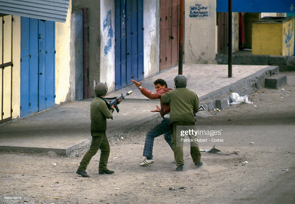 Two armed soldiers on patrol arrest a Palestinian man in the streets. Violence broke out after rebel Israeli and Palestinian fighters protested in the occupied territory of Gaza during the first Intifada.