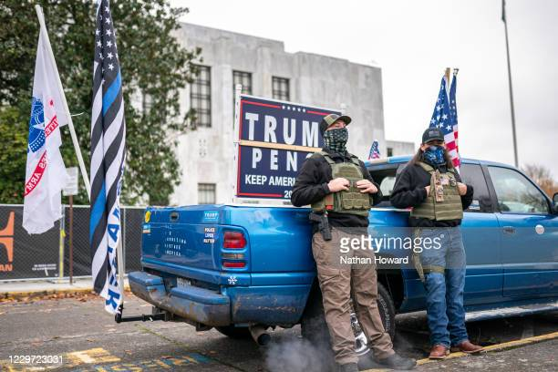 Two armed supporters of President Donald Trump lean on their truck at a 'Stop The Pause and Defeat The Steal' rally in front of the state's capitol...