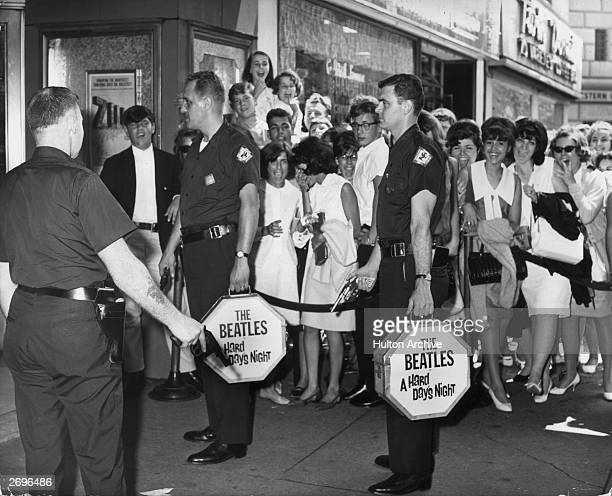 Two armed Wells Fargo guards carry canisters with prints of director Richard Lester's film, 'A Hard Day's Night,' starring the rock group The...
