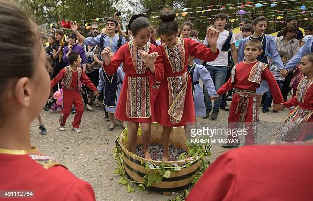 Two Armenian girls dance while treading grapes with their bare feet during a wine festival in the village of Rind some 100 kms outside Armenia's...