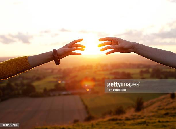Two arms reaching together at sunset.