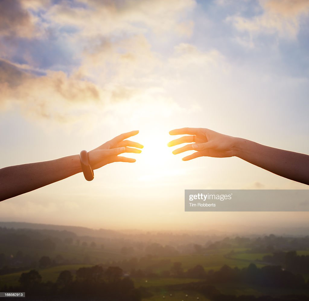 Two arms reaching together with sun. : Stock Photo
