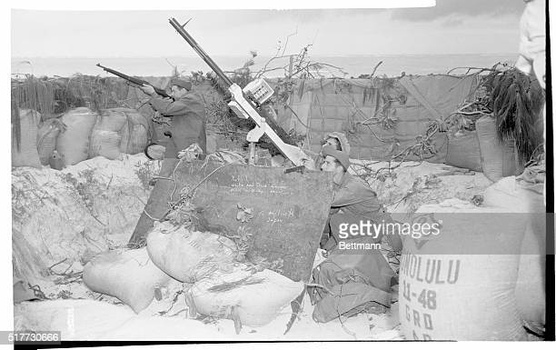 Two Army gunners fire at diving Jap planes with heavy antiaircraft machine gun while soldier in background uses rifle A metal plate forms a shield...