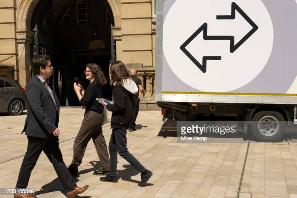 Two arrows on the side of a van pointing in different directions as people pass by on 15th June 2021 in Birmingham, United Kingdom. The scene is one...