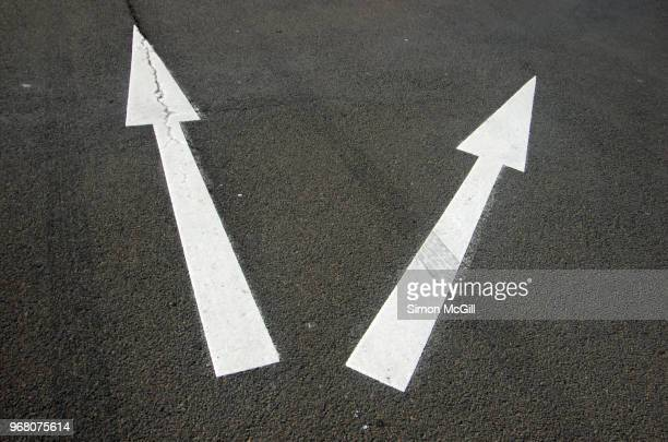 Two arrows pointing in different directions on a road