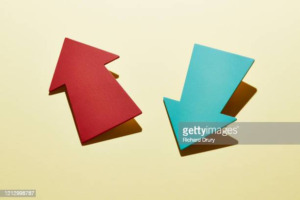 two arrows pointing in different directions - fighting stock pictures, royalty-free photos & images