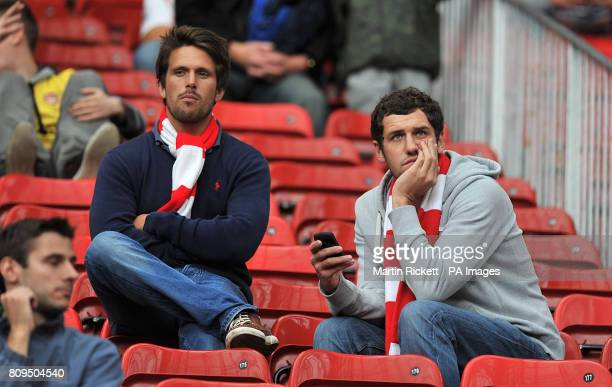 Two Arsenal fans look dejected in the stands during the Barclays Premier League match at Old Trafford Manchester