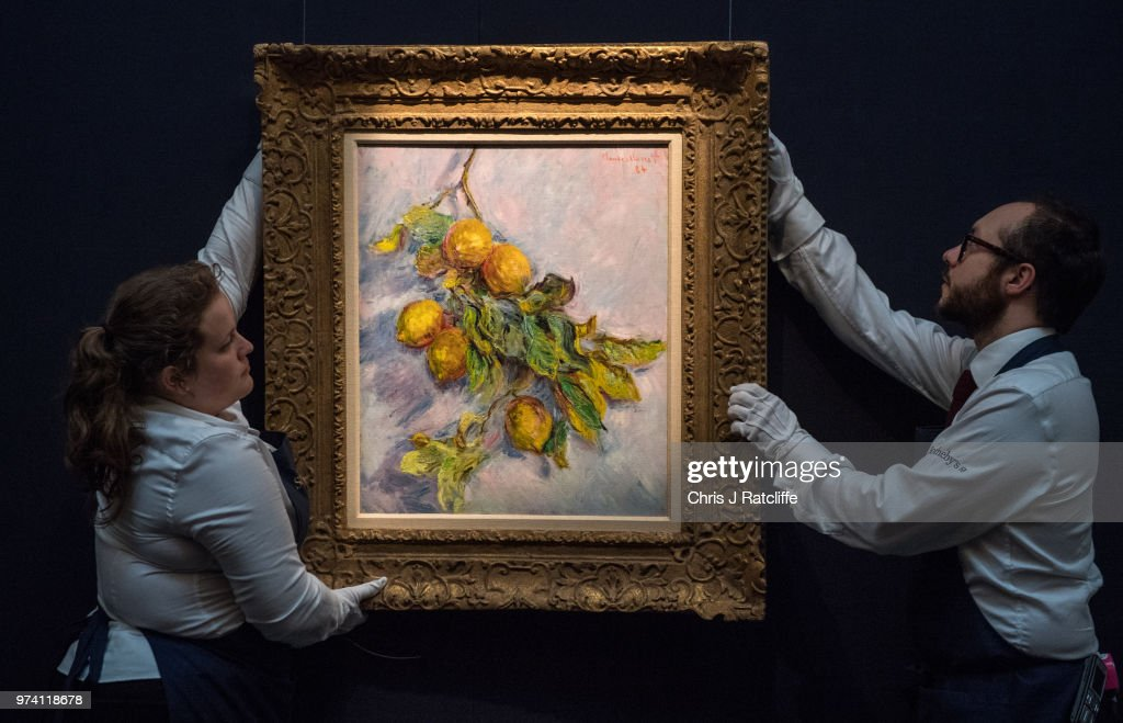 Two art handlers hang 'Citrons sur une branche' by Claude Monet (estimated at £2.5 million to £3.5 million) during a preview of the Impressionist and Modern sale at Sotheby's on June 14, 2018 in London, England. The sale will take place on 19 June 2018 and includes works by artists Picasso, Monet, Kandinsky and Matisse.