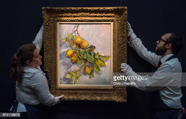 Two art handlers hang 'Citrons sur une branche' by Claude Monet during a preview of the Impressionist and Modern sale at Sotheby's on June 14 2018 in...