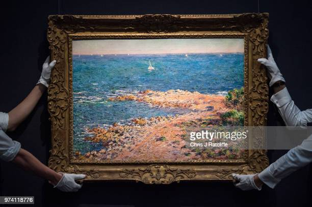 Two art handlers hang 'La Mediterranee par vent de mistral' by Claude Monet during a preview of the Impressionist and Modern sale at Sotheby's on...