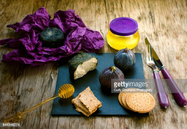 Two artisanal goat cheeses chevre in various coating: grape leaves and charcoal or ash with wholegraine crispbread,