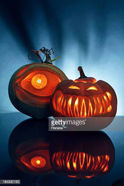 two artistically carved jack-o-lantern pumpkins - halloween pumpkin stock photos and pictures