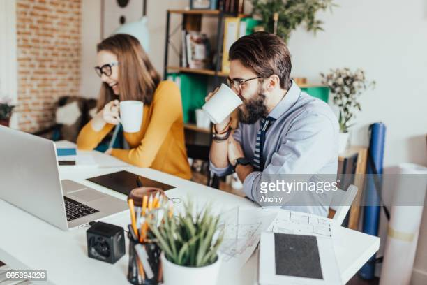 Two artists both drinking tea from the mugs