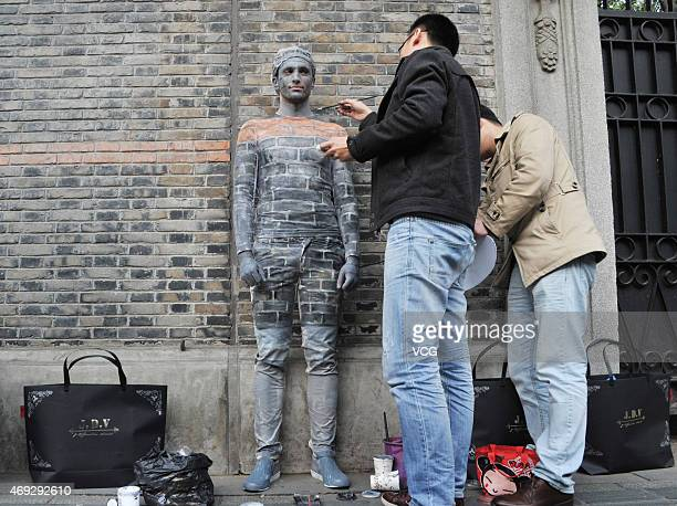 "Two artists paint a boy disguised as a wall near New World street on April 10, 2015 in Shanghai, China. A boy ""hides"" himself by being painted the..."